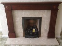 Beautiful wooden fireplace with marble hearth, surround and fire