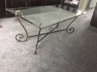 Glass coffee table with metal scroll effect base