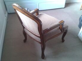 Large upholstered wooden framed accent chair with decorative carved detailing.