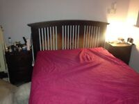 Solid dark wood double bed frame with matching bedside cabinets