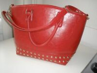 Big red bucket bag with studs.