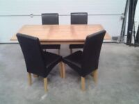 New extendable table and 4 black chairs. Less 1/2 price Can deliver.