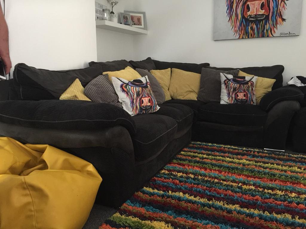 Large black corner sofa and foot stool