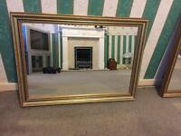 Medium sized gold mirror with wide border