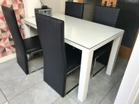 White glass top table and 4 black chairs