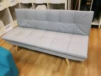 Cream fabric sofabed with wooden legs