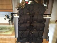 Size 8 ladies gillet with zip and toggles with removable fur on lined hood. BARGAIN PRICE. COSY.