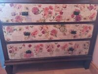 Vintage chest of drawers with distressed floral pattern.