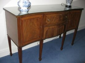 Mahogany serpentine front sideboard on raised legs, 151 cm. Early 20C. 2 drawers, 2 cupboards.