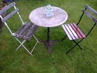 beautifully weathered garden or patio marble top cast iron table with two folding chairs