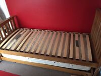 Wooden frame single bed with mattresses and pull out bed