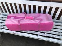 Pink travel cot in bag