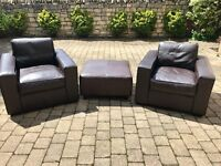 Two dark brown leather arm chairs with brown leather foot stall