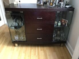 Solid three drawer with two glass display unit with chrome handles and feet