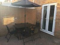 Glass top garden table, 6 chairs and parasol