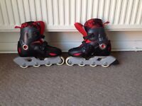 Red and black in-line skates. Adjustable to fit size 1.5 to 3.
