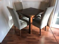 dining table and four high back fabric chairs. Purchased from The Store, linen color chairs.