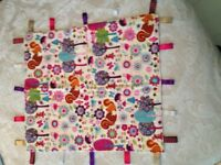 Taggies, made from cotton fabric with various ribbons attached. Size 54cm x 49cm cost £4.00