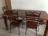 Large wooden and metal dining table, 4 matching chairs.