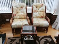 2 conservative chairs with a coffee table and footstool.