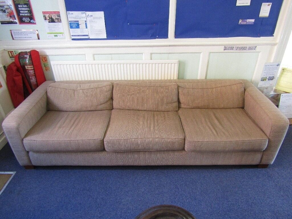 Large light brown three-cushion sofa with shallow wooden feet