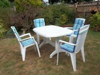 White oval table with 4 chairs and cushions.