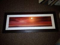 Brown leather effect framed beach scene in reds tones.