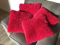 4 red fluffy cushions