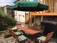 As new, teak garden table and 6 chairs plus parasol with base