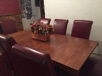 Large teak family table and 8 red faux leather chairs