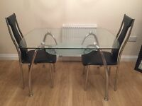 Glass dining table with under shelf and two black chairs