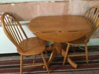 Round table and two wheel back chairs in light wood excellent condition