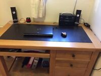 Oak work desk with leather writing insert, three draws and under top pull out.