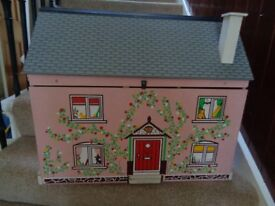 This is a wooden dolls house, signs of wear but still in good condition