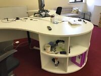 Two white stylish office desks with curved sides and shelves