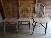 Three solid oak wheel back dining chairs