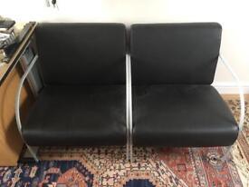 A pair of black vinyl chairs