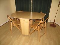 Wooden dining table and 4 fold up chairs. The table seats 4 people.