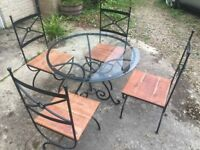 Glass topped, wrought iron dining table and four chairs