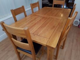 Solid oak extending dining table with 6 chairs.