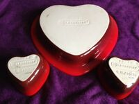 Brand New 3 Le Creuset red stoneware heart shaped dishes. 2 small ramekins and 1 large baking dish.