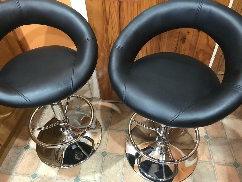 Pair of black gas lift bar stools.