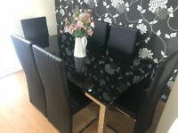 For sale and in excellent condition a black glass dining room table and six chairs.