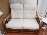 Cane sofa with cream cushions for conservatory in good condition