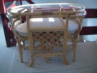Cane furniture including glass top table and two chairs with cushions