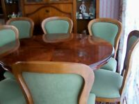 Round dining table with patterned top and pedestal leg and six green velvet chairs