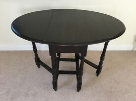 Oval dark wood gate-legged table with turned legs