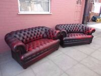 A pair of red leather chesterfield buttoned sofas