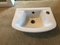 White cloakroom basin complete with fixing bolts.