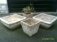 Four weathered concrete planters.
